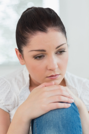 Thoughtful woman sitting on the couch in a living room and looking sad photo