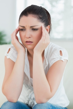 uneasiness: Mujer tensionada que se sienta en el sof� de una sala de estar y tomados de la mano contra la cabeza
