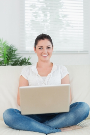 Smiling woman using a laptop while sitting on the couch in the living room photo