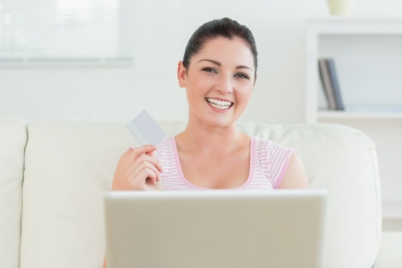 Woman sitting in a living room on a couch and holding a credit card while using a laptop photo