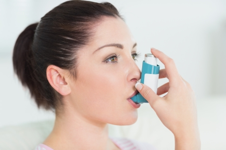 bronchial: Woman having asthma using the asthma inhaler for being healthy Stock Photo