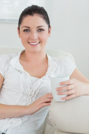 Happy woman holding a cup while sitting on a couch in a living room and relaxing photo