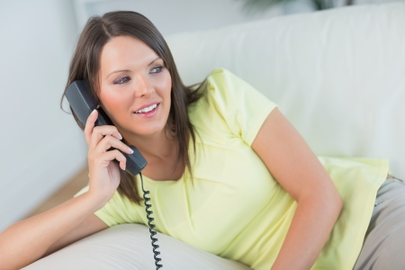 smiling woman sitting in her sofa and calling somebody in the living room photo