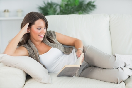 Happy woman lying on sofa and reading her book in the living room photo
