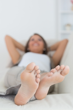 Woman relaxing at home with her feet up on the sofa photo
