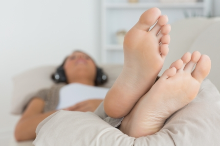 Woman with her feet up listening to music on the sofa photo