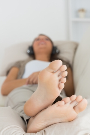domiciles: Woman listening to music with her feet up on the couch Stock Photo