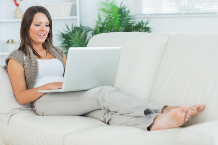 woman laptop: Cheerful woman lying on the sofa and using her laptop in the living room Stock Photo