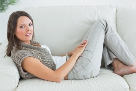 Happy woman relaxing on sofa at home photo