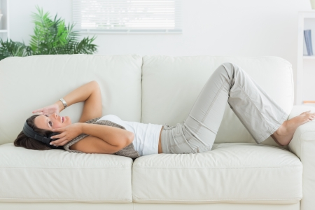 Happy woman lying on the sofa and listening music in the living room  photo