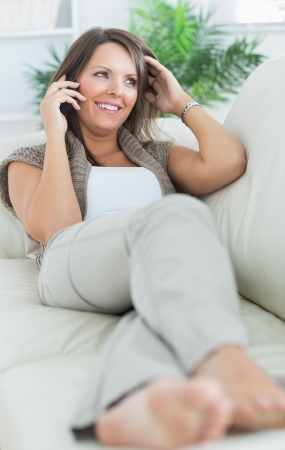 Happy woman lying on sofa and calling in the living room photo