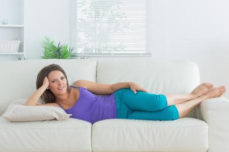 recline: Happy brunette lying on sofa in the living room