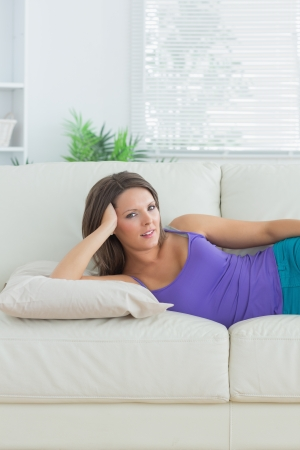 Calm brunette lying on sofa in the living room Stock Photo - 16054664