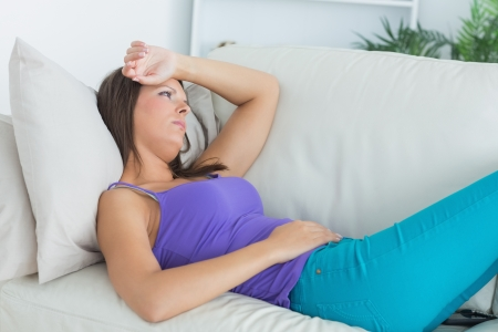 Anxious woman lying on sofa in the living room photo