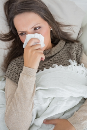 Sick woman holding tissue to nose on the couch photo