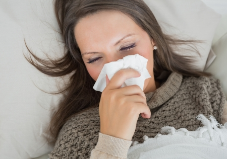 Sick woman lying on sofa and blowing nose in the living room photo