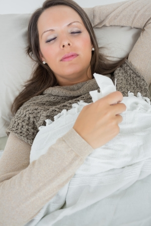 Sleeping woman lying on sofa with a cold in the living room photo