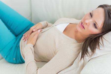 dolor de estomago: Mujer enferma acostada en el sof� en la sala de estar con dolor stomahc