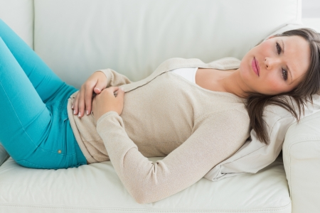 upset stomach: Anxious and sick woman lying on sofa in the living room