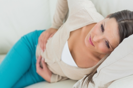upset stomach: Woman lying on sofa looking sick in the living room