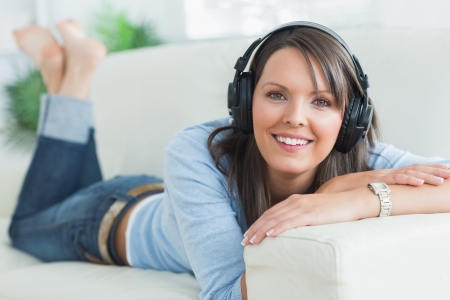 Woman listening music looking happy on sofa in the living room photo