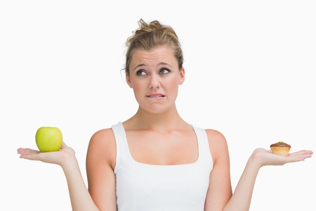 Woman holding apple and cupcake deciding to eat healthily or not