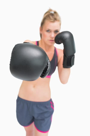 Female boxer standing stretching arm out for punch photo