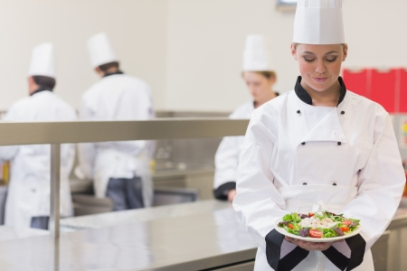 Chef presenting her salad in the kitchen photo