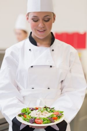 Cheerful chef looking at her salad in the kitchen photo