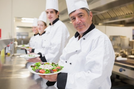 Cheerful Chef's showing their salads in the kitchen  photo