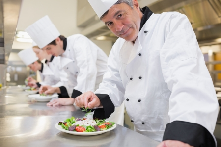 female chef: Smiling Chefs preparing their salads in the kitchen  Stock Photo