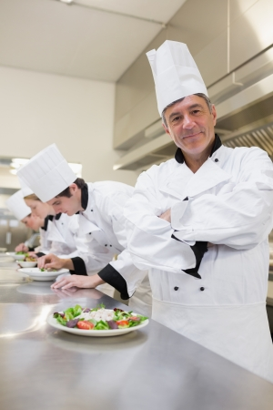 Happy ched with others preparing salads in the kitchen photo