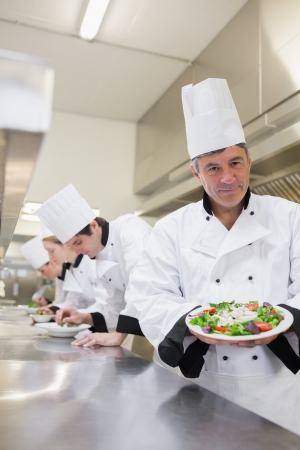 Cheerful chef showing his salad with workers in background in the kitchen  photo
