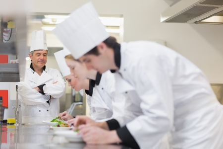 chefs whites: Chef supervising others making salads in kitchen