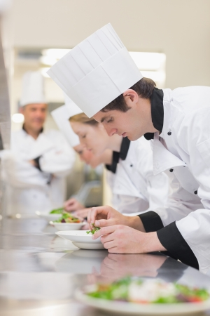 Culinary class preparing salads as teacher is supervising photo