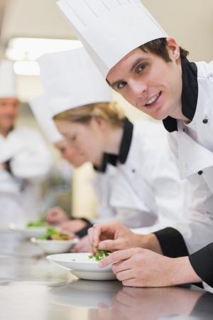 Chef-kok te kijken van de voorbereiding salade in culinaryclass en glimlachend