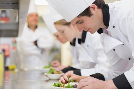kulinarne: Culinary class w kuchni podejmowania sałatki jako nauczyciel jest z widokiem Zdjęcie Seryjne