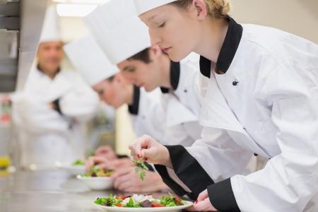 Trainne Chefs preparing salads in class in kitchen photo