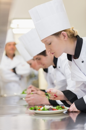 finishing touches: Chefs applying finishing touches to salads as head chef is watching