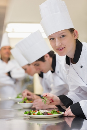 Smiling chef looking up from preparing salad in culinary class photo
