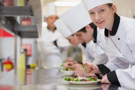 chef cocinando: Cocinero feliz mirando hacia arriba desde la preparaci�n de la ensalada en clase de cocina