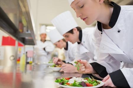 Kocken avslutar sin sallad i kulinariska klass i köket Stockfoto