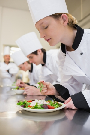 Chef preparing a salad in culinary class in kitchen Stock Photo