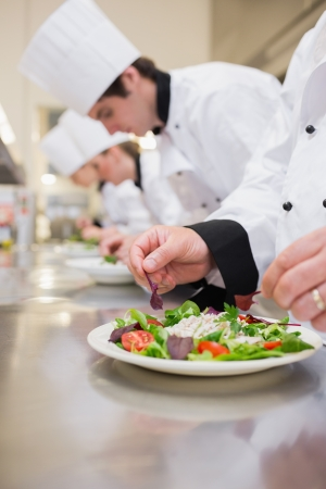 chefs whites: Salad being garnished by chef in the kitchen