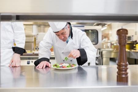 chefs whites: Chef garnisning his salad in kitchen
