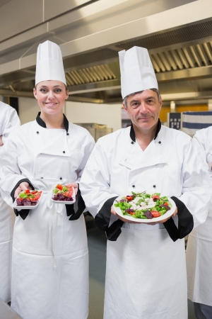 Chef's presenting their salads in the kitchen photo