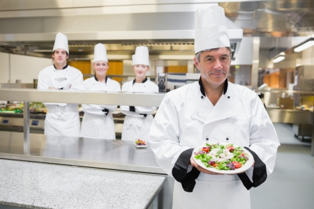 Head chef presenting salad with his team standing behind him  photo