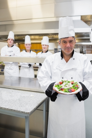 Head chef showing a salad with his team standing behind him photo