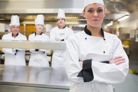 chefs whites: Chef standing with crossed arms with team standing behind Stock Photo