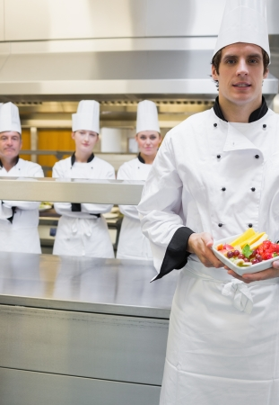 Chef presenting fruit salad with team standing behind him photo